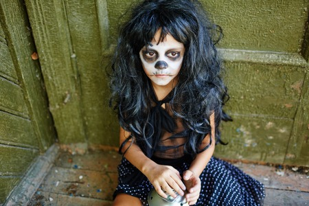 haunted: Sad girl with artificial hair sitting by wall of haunted house