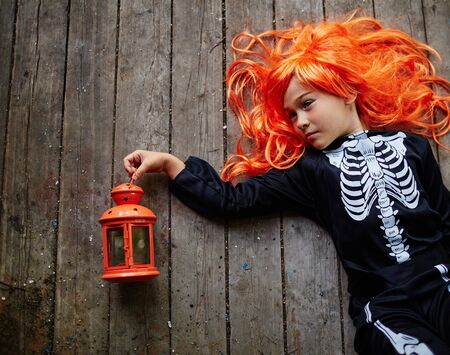 holiday tradition: Relaxed girl in orange wig and Halloween attire lying on wooden floor