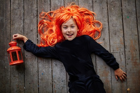 attire: Cheerful little girl in orange wig and black attire looking at camera while lying on wooden floor