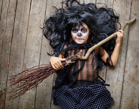 repent: Little witch with broom looking at camera Stock Photo