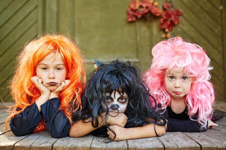 wigs: Group of cute girls in wigs looking at camera Stock Photo
