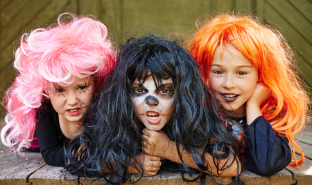 wigs: Small frightening witches in wigs looking at camera
