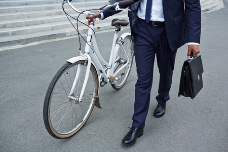 going: Businessman with briefcase and bicycle going to work