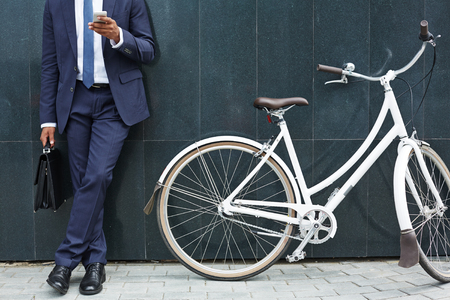 Close-up of modern businessman with cellphone standing by wall of modern building with bicycle near by