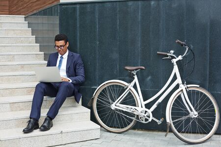 technology career: Modern employee sitting on stairs and networking outdoors