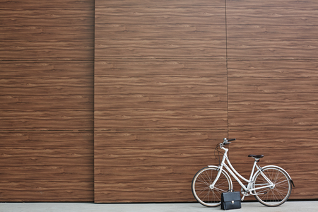 black briefcase: Bicycle and black briefcase against wooden wall Stock Photo