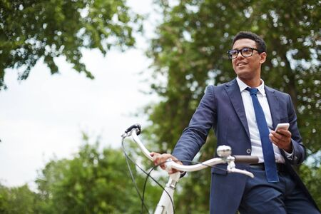 break in: Young businessman with cellphone and bicycle having break in park