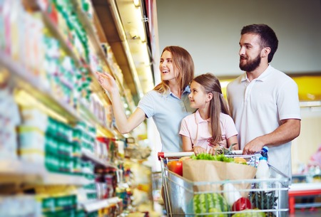shopping cart: Young family in hypermarket choosing products