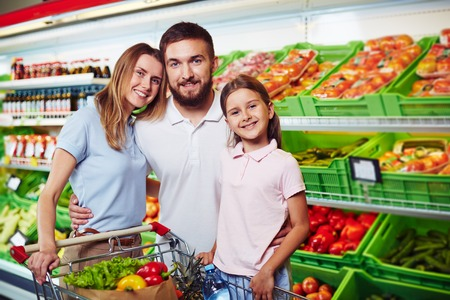 Family of three looking at camera in supermarket