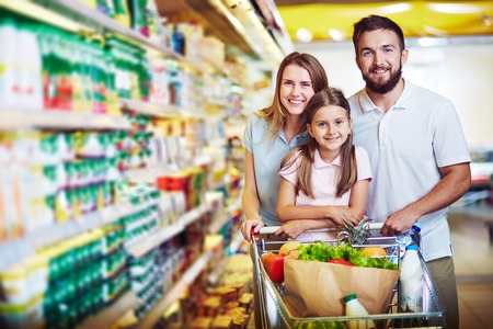 Joyful family of father, mother and daughter looking at camera in supermarket