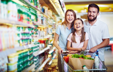 woman shopping cart: Ecstatic family with shopping cart with food visiting supermarket