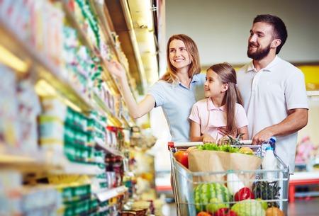 family: Familia feliz que elige los productos lácteos en el supermercado Foto de archivo