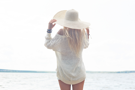 seaside: Young woman in hat and white pullover having rest by the sea