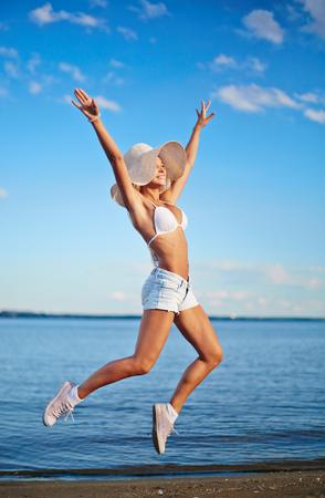 sunhat: Happy girl in bikini, denim shorts and sunhat jumping by the seaside Stock Photo