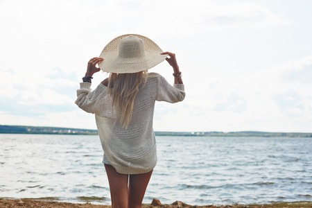 seashore: Back view of young woman in hat and white pullover standing by the sea