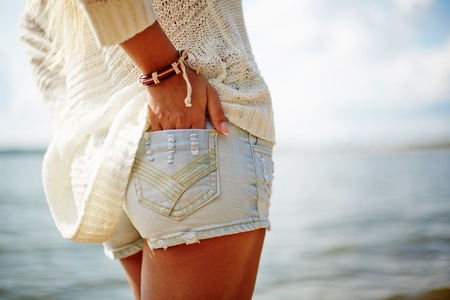 Rear view of female in denim shorts with her hand in its pocket