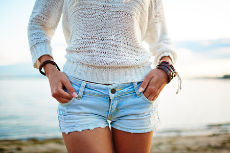 jeanswear: Close-up of young woman in white pullover and denim shorts