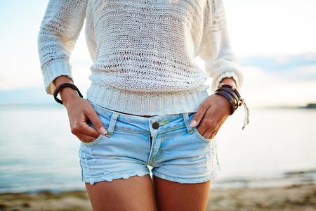 pantalones cortos: Primer plano de una mujer joven en el suéter blanco y pantalones cortos de mezclilla