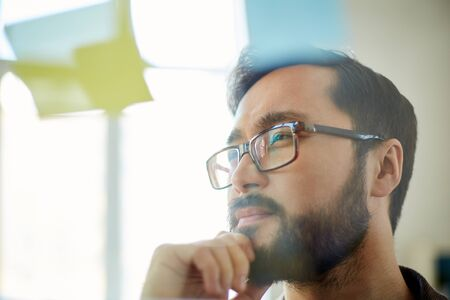 beard man: Pensive businessman looking at reminder in office Stock Photo