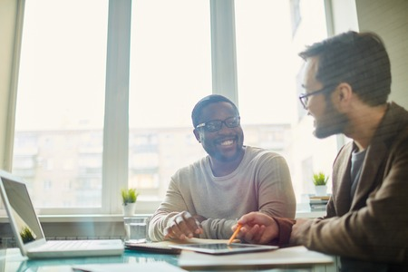 associates: Contemporary businessmen interacting at meeting Stock Photo