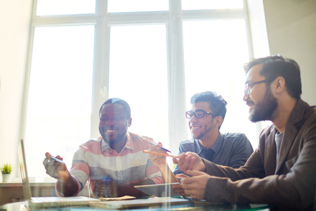 discussion: Group of employees pointing at laptop display while discussing project Stock Photo