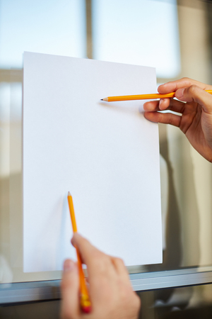 paper board: Blank paper on notice board and hands with pencils pointing at it Stock Photo