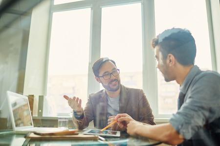彼のアイデアや意見を同僚に説明するビジネスマン 写真素材