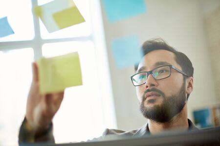 reminder: Young modern businessman looking at reminder with working plan