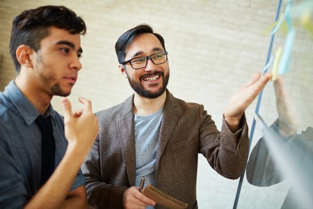 Asian businessman pointing at reminder while explaining his viewpoint to colleague 스톡 콘텐츠