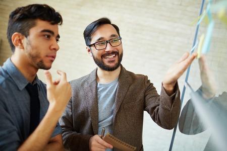 Aziatische zakenman die op herinnering, terwijl het uitleggen van zijn standpunt naar collega