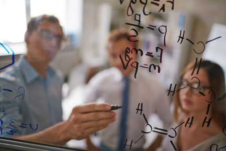 formulae: Businessman writing formulae on transparent board