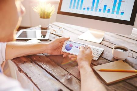 analyzed: Marketing data in smartphone being analyzed by employee Stock Photo