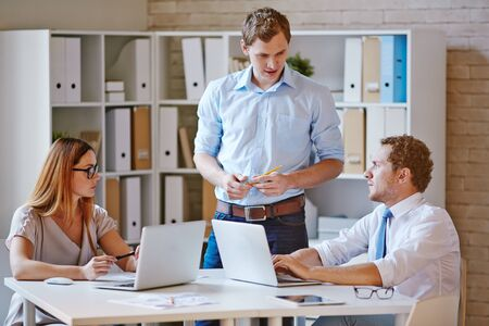 discussing: Confident co-workers discussing plans in office Stock Photo