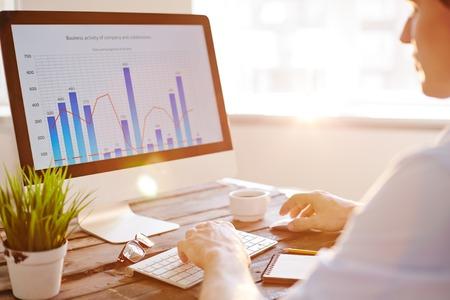 trabajando en computadora: El hombre de negocios que se sienta delante de monitor de la computadora y el análisis de datos Foto de archivo