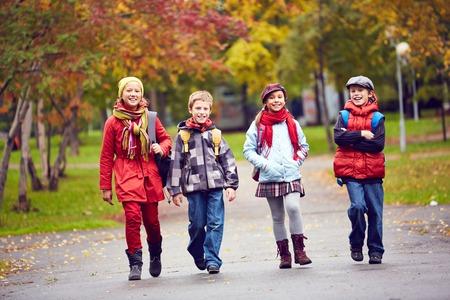 schoolkids: Group of happy schoolkids going to school