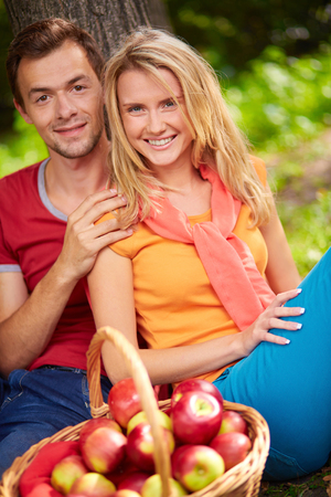 couples outdoors: Amorous couple sitting by tree with basket full of ripe apples in front