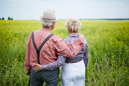 persona caminando: Vista posterior de la pareja de ancianos tomando un paseo por el campo