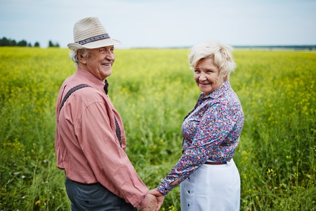 happy seniors: Happy seniors holding by hands in the field