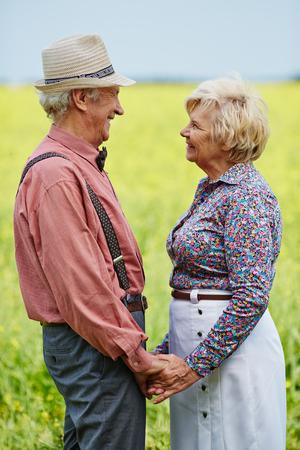 familias unidas: Hombre mayor y mujer que sostiene con las manos y mirando el uno al otro en el campo