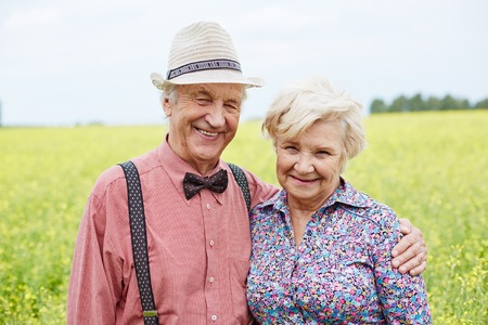 happy seniors: Affectionate and happy seniors looking at camera outdoors Stock Photo
