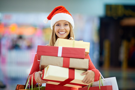 christmas gift: Portrait of a young woman holding gift boxes