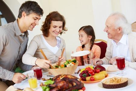 familia comiendo: Mujer que da la ensalada a su hija