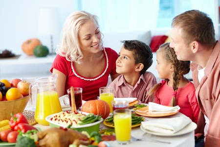 feast table: Family of four gathering at dinner table Stock Photo