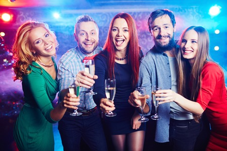 Blije vrienden drinken van wijn in nachtclub Stockfoto