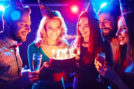 誕生日ケーキの周りの若い人たち