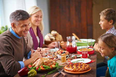 personas reunidas: Los padres que se sientan a la mesa con sus niños pequeños