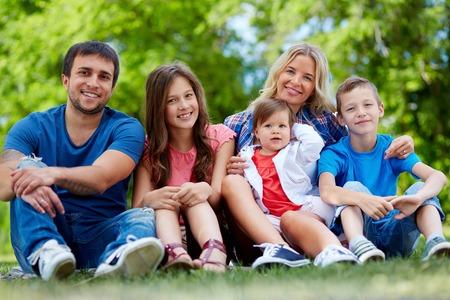 trois enfants: Heureux parents posant avec trois enfants