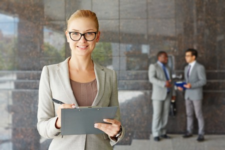 men and women: Young seriously looking businesswoman smiling at camera Stock Photo
