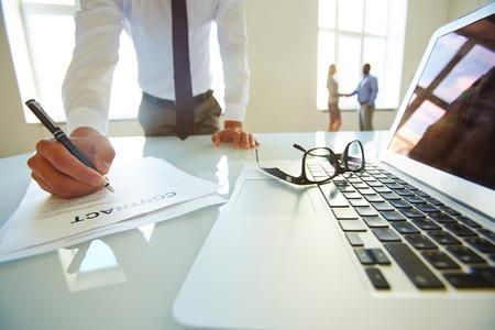 Advocaat lezen contract terwijl partners bespreken voorwaarden op de achtergrond