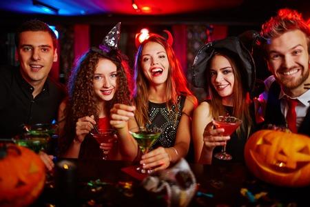 Friends resting in nightclub at Halloween